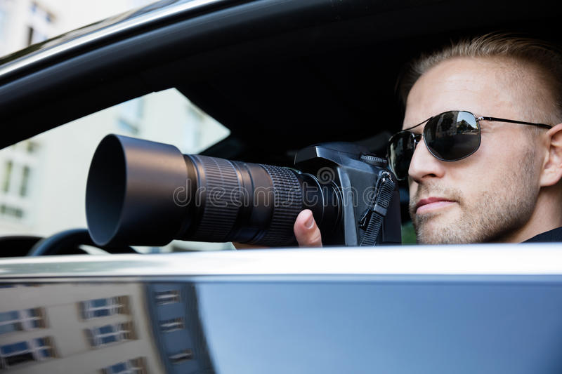Man Photographing With SLR Camera. Private Detective Sitting Inside Car Photographing With SLR Camera royalty free stock image