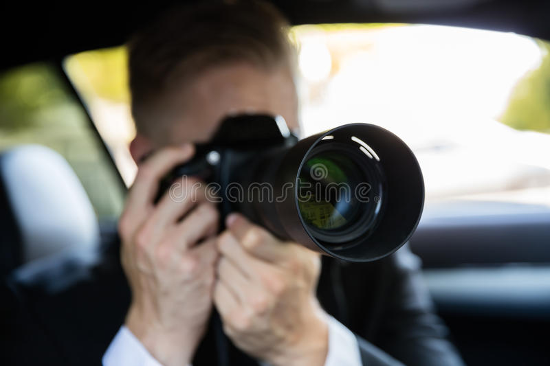 Man Photographing With SLR Camera. Private Detective Sitting Inside Car Doing Surveillance Work Photographing With Camera royalty free stock images