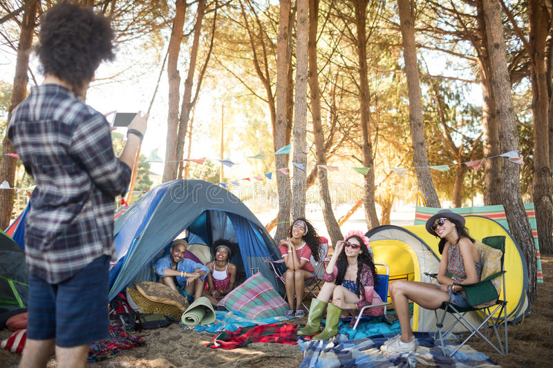 Man photographing smiling friends at campsite. Man photographing smiling friends by tents at campsite royalty free stock photo