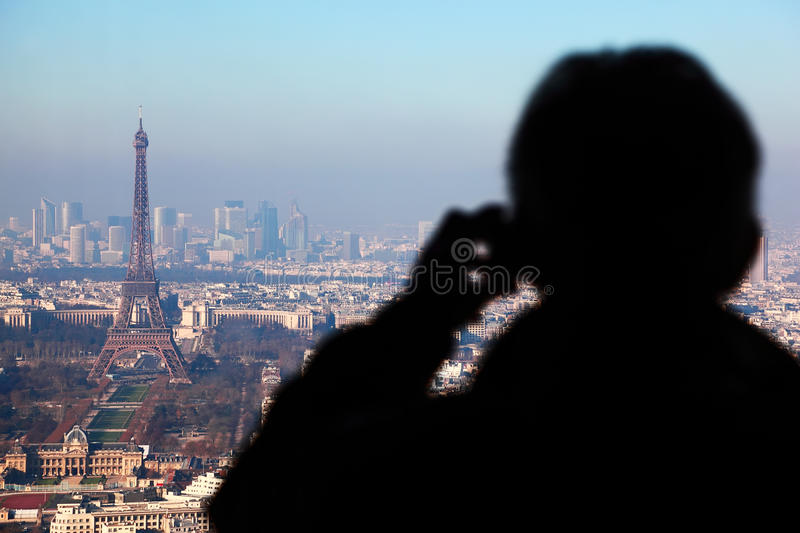 Man photographs panorama of Paris. With Eiffel tower, la Defence at winter, France royalty free stock photography