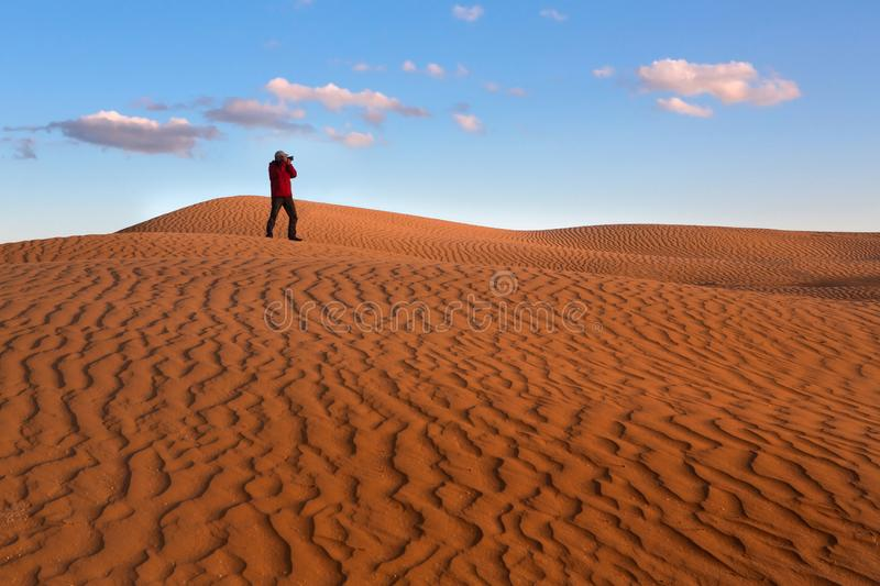 A man photographs the sand dunes of the desert. Photographer in the desert. Yellow sand, blue sky royalty free stock photo