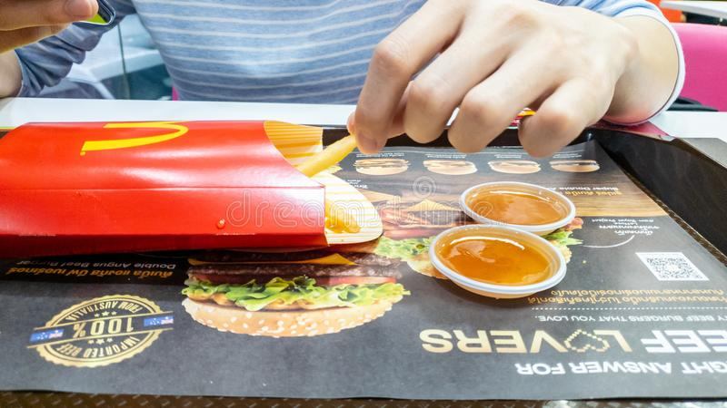 A man picking french fries container in red package and chili sauce on advertising paper in tray mat at McDonald`s cafe royalty free stock images