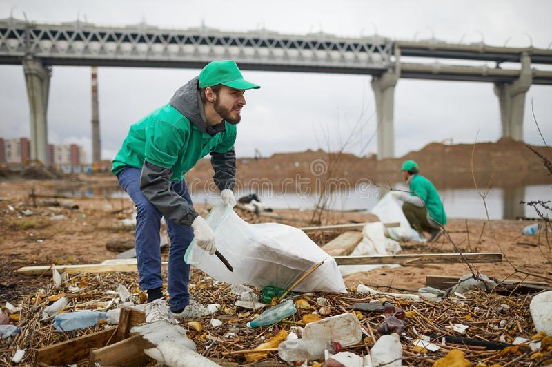 Man picking garbage on polluted shore. Young bearded men in green uniform collecting litter on coast stock images