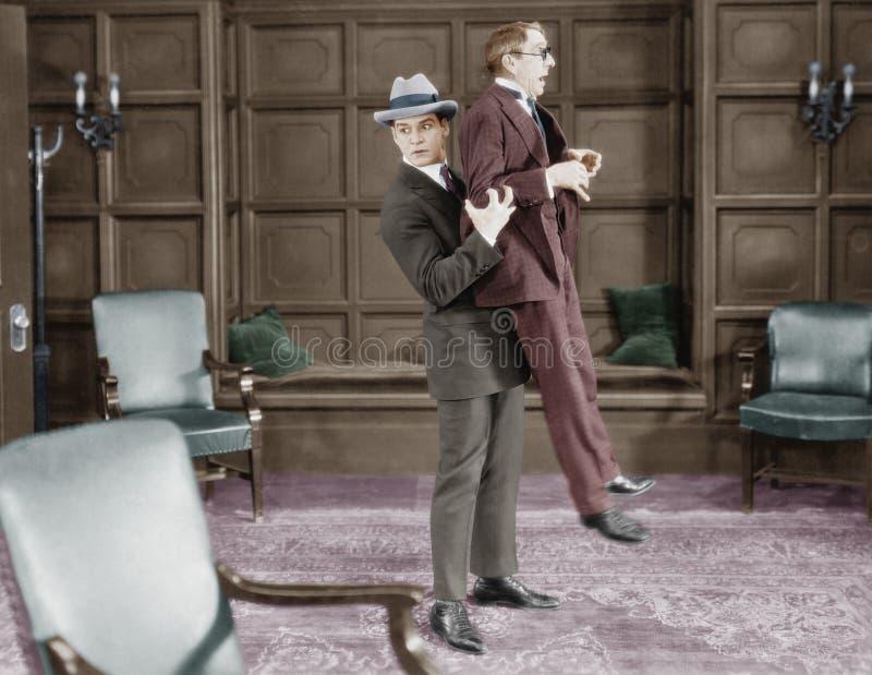 Man picking up frightened man stock image
