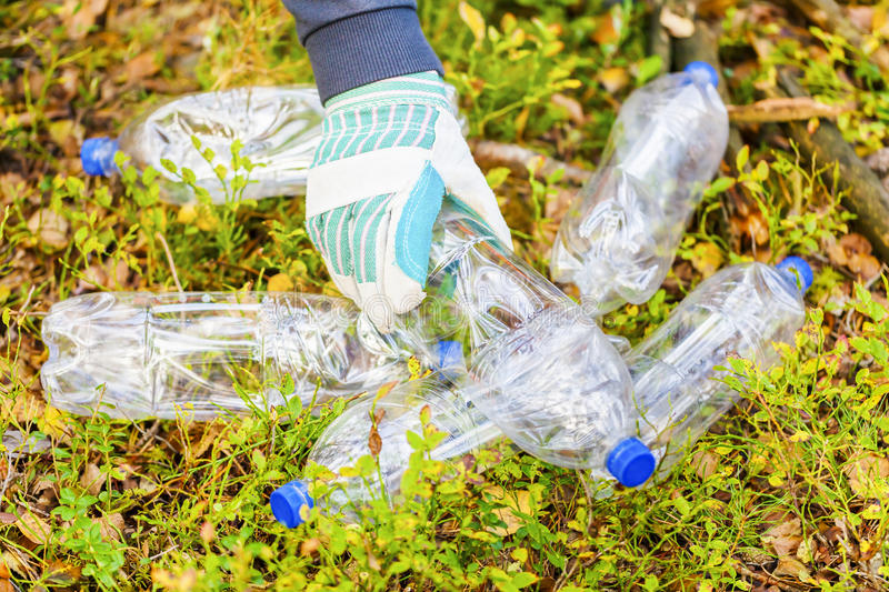 Man picking up used plastic bottles in forest. In backgrounds stock photo