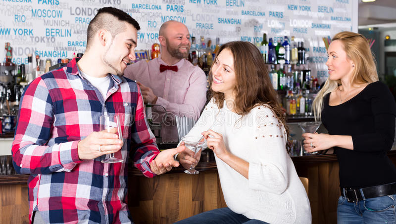 Man picking up woman in bar. Handsome young men picking up a beautiful women in a bar. Man and women are chatting and the cheerful barman is pouring a drink for royalty free stock photo