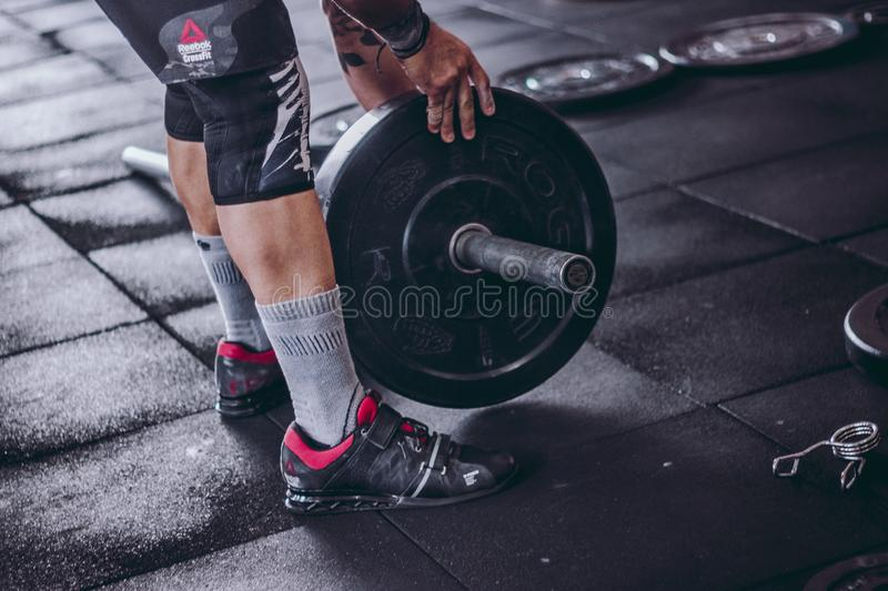 Man Picks Up Black and Grey Barbell royalty free stock photography