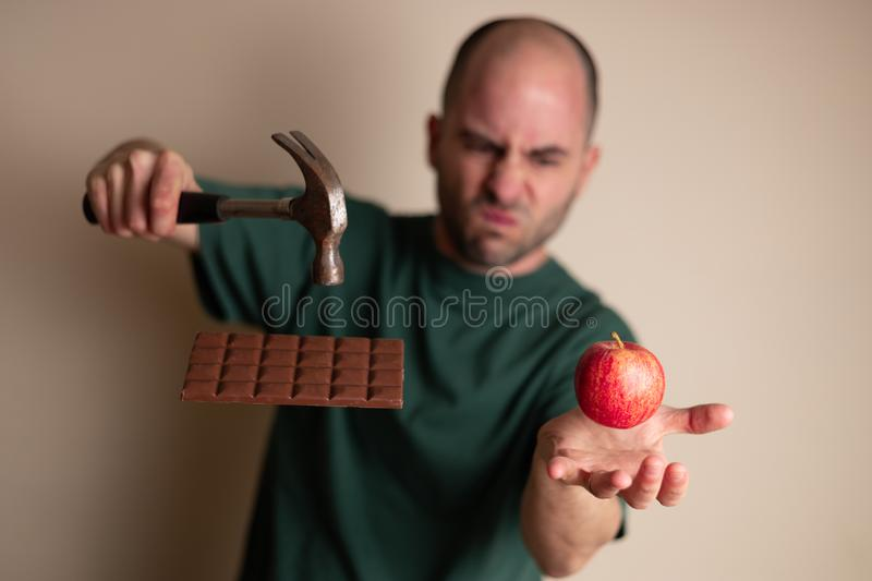 Man picks up a hammer to smash a chocolate bar with one hand and hold an apple with the other, stock photo