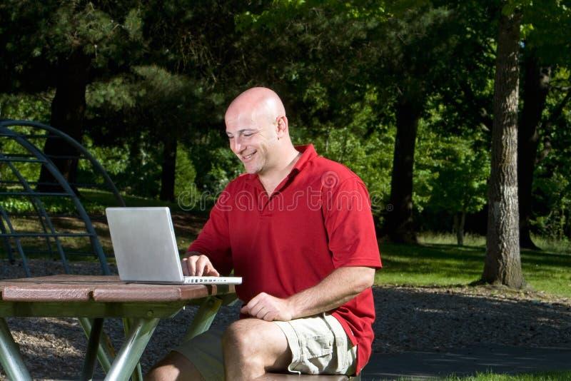 Download Man At Picnic Table On Computer - Horizontal Stock Images - Image: 5607604