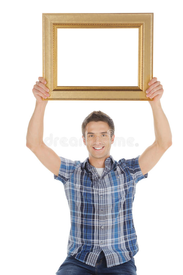 Man with picture frame. Handsome young man holding a picture frame and smiling at camera while isolated on white royalty free stock photos