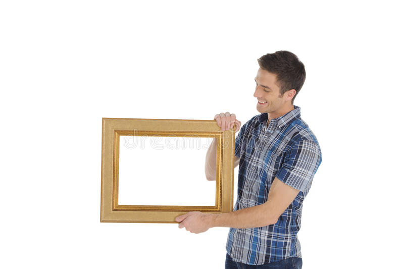 Man with picture frame. Handsome young man holding a picture frame and smiling while isolated on white stock photography