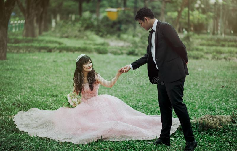 Man in 2-piece Suit Holding Woman in Peach-colored Wedding Gown White Holding Her Flower Bouquet stock image