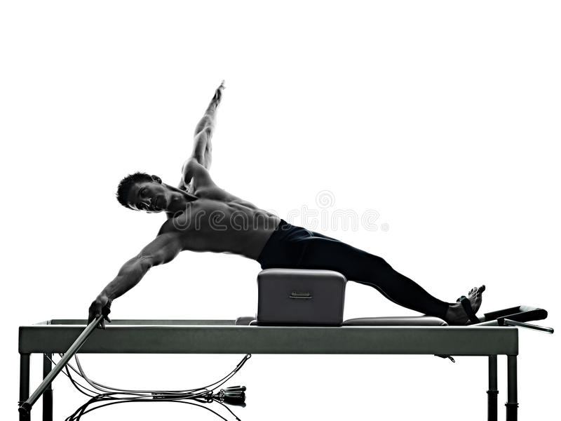 Man pilates reformer exercises fitness isolated. One caucasian man exercising pilates reformer exercises fitness in silhouette isolated on white backgound stock photo