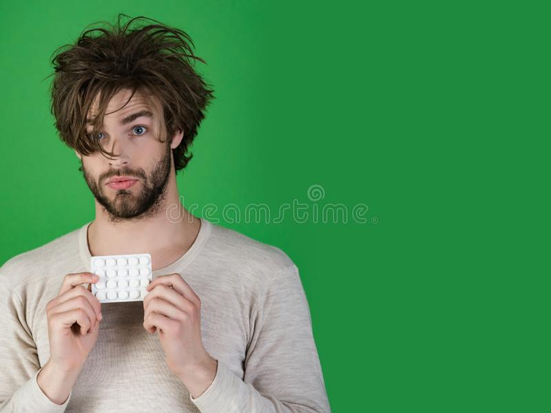 Man with pills in blister pack, cold and flu, insomnia. Man with pills in blister pack has uncombed hair in morning on green background, health and medicine stock images