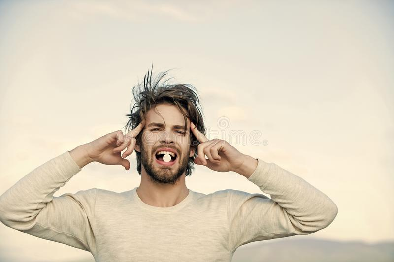 Man with pills in blister pack, cold and flu, insomnia. Man with pill in mouth has uncombed hair in morning outdoor on sky background, health and medicine stock image