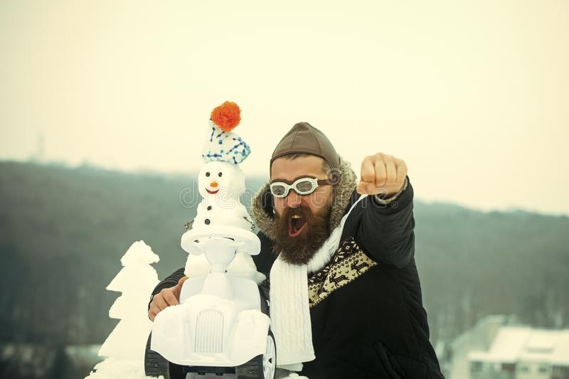 Man in pilot hat and glasses with raised fist hand. Excited hipster shouting on winter landscape. Snowman driving toy car on white sky. Christmas and new year stock photo