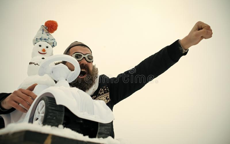 Man in pilot hat and glasses with raised fist hand. Solidarity and support concept. Excited hipster on white sky. Snowman driving toy car on snowy table stock photo