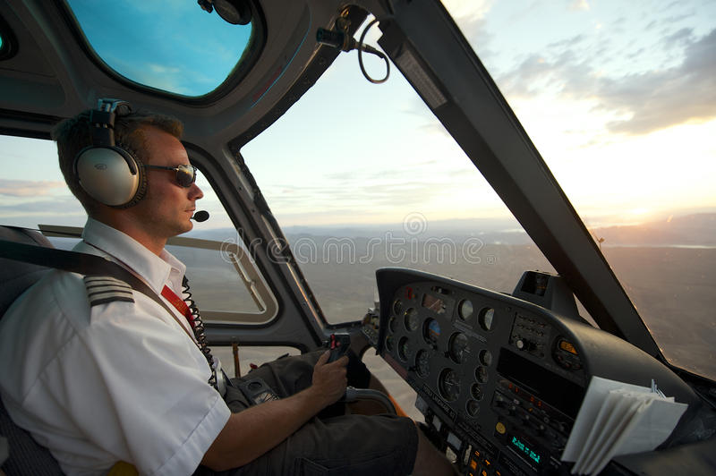 Man pilots helicopter to Grand canyon at sunset, circa Las Vegas, USA. stock photos