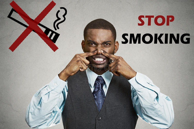 Man, pinches his nose, something stinks bad smoke smell. Portrait young man, pinches his nose, something stinks bad smoke smell, grey wall background, stop royalty free stock photos