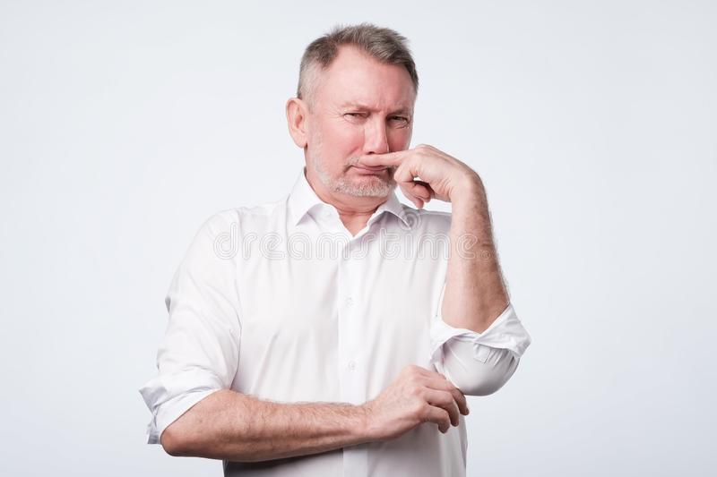 Man pinches nose with finger looks with disgust something stinks bad smell royalty free stock image