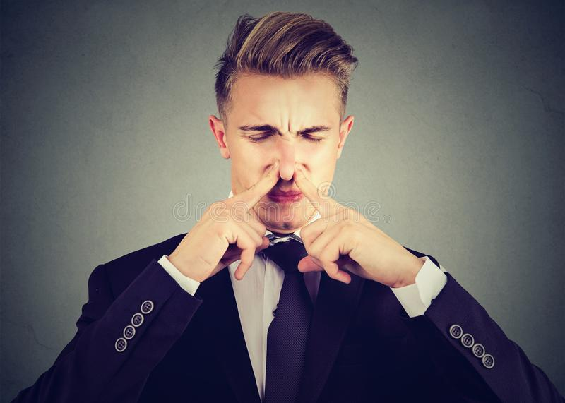Man pinches nose with fingers looks with disgust something stinks bad smell. Man pinches nose with fingers looks with disgust something stinks bad smell royalty free stock photos