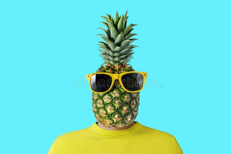 A man with a pineapple instead of head. Minimal summer concept stock photography