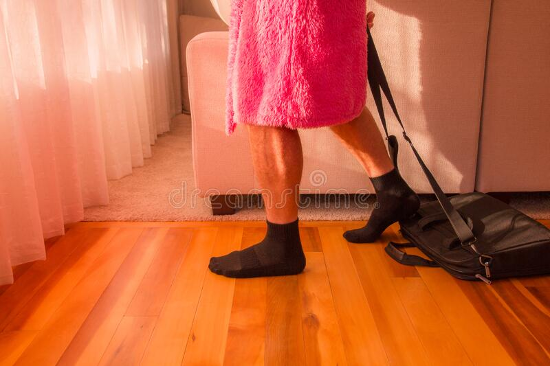 Man in pink dressing gown going to work at home office during coronavirus self isolation stock photos
