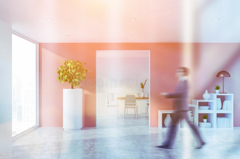 Man in pink living room with bookshelves. Man walking in interior of minimalistic living room with pink walls, concrete floor and white bookshelves with lamp and stock photo