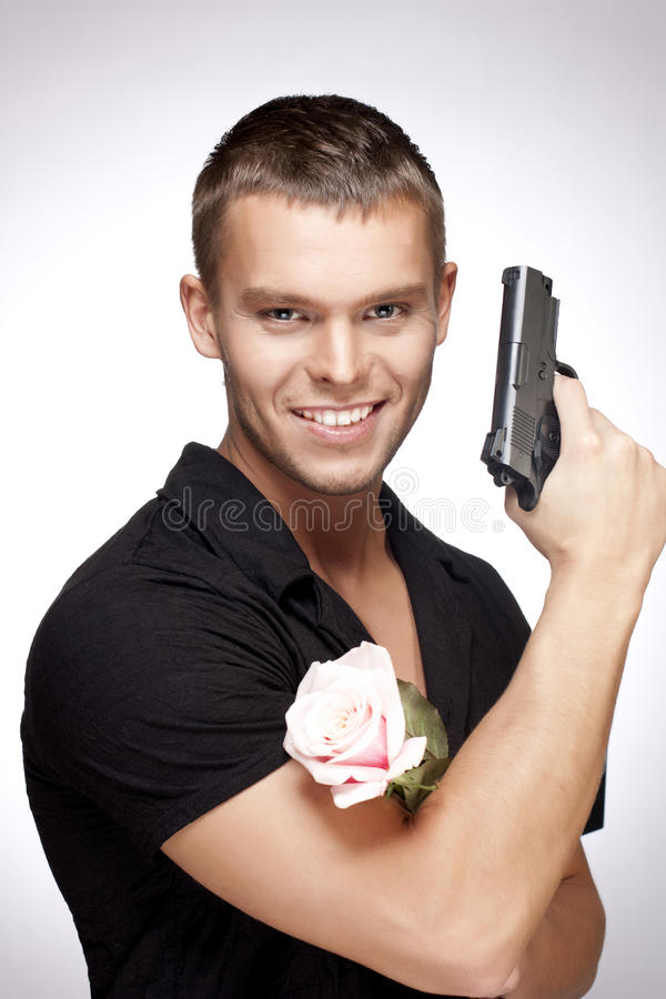 Man with pink rose and gun stock photo