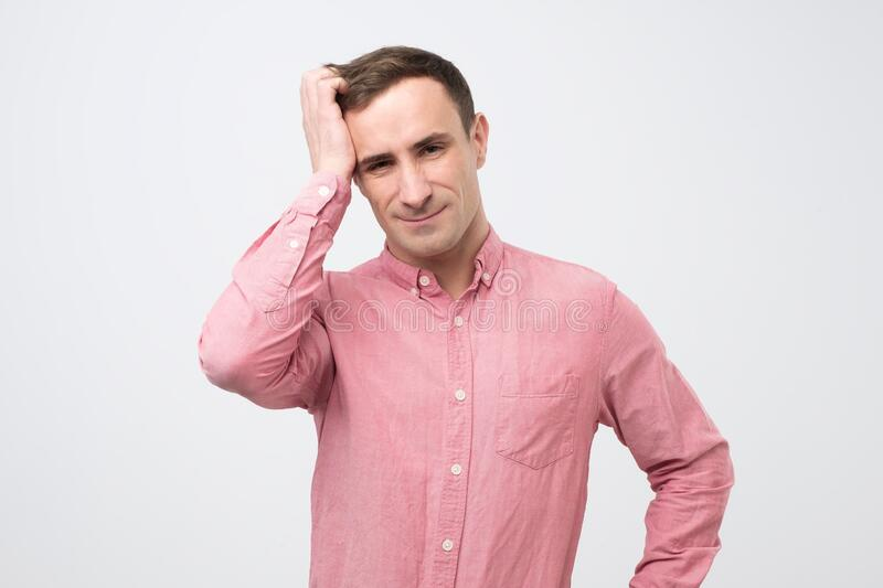 Man in pink shirt being shocked, he try to remember important in formation before meeting. Young handsome caucasian man in pink shirt being shocked, he try to royalty free stock photos