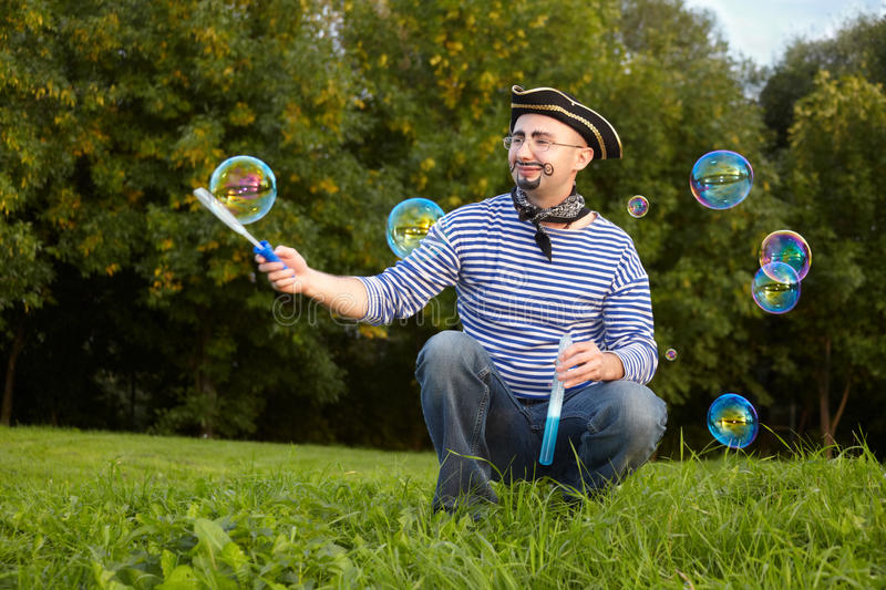Man in pirate suit is blowing soap bubbles stock photos