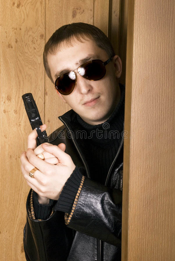 Man with a pistol peeking out from a door stock photo