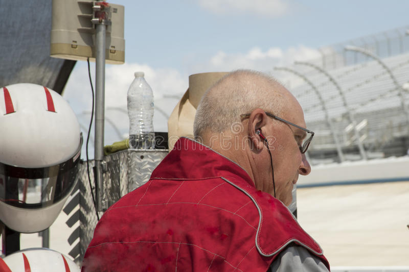 Man on pit row ready to drive IRL car. Man in race suit on pit row at motor speedway before driving race car royalty free stock image
