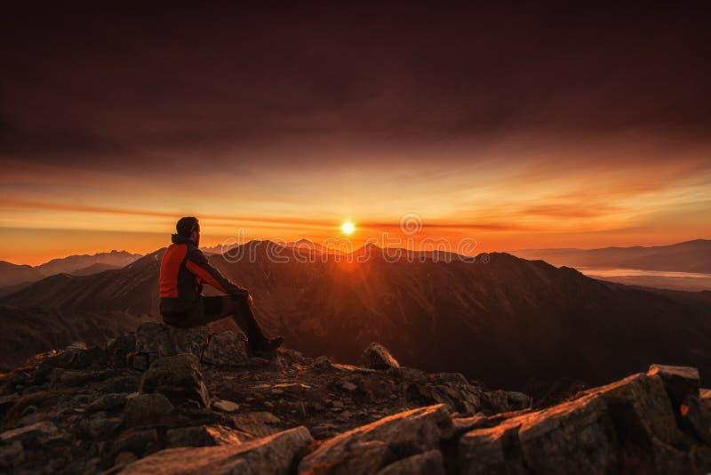 Man placering på överkanten av berget på soluppgång som fotvandrar och klättrar arkivbild