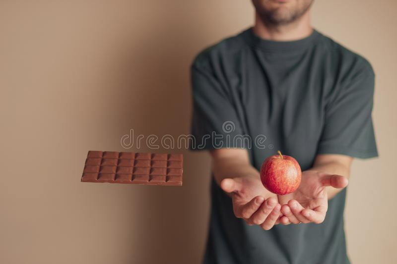 Man places hand underneath floating apple while ignoring a chocolate bar, stock photos