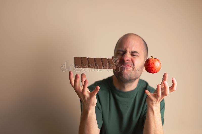 Man places one hand underneath a chocolate bar and the other underneath an apple royalty free stock photos