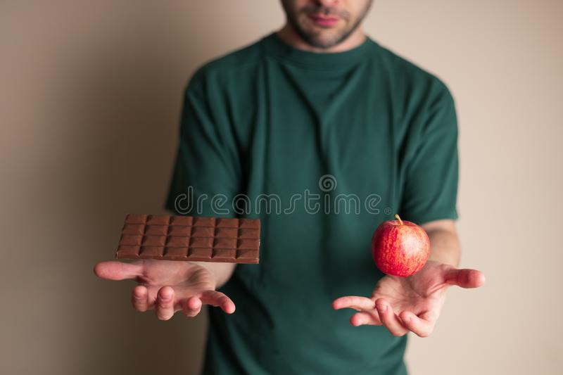 Man places one hand underneath a chocolate bar and the other underneath an apple stock photos