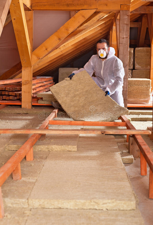 Man places rockwool thermal insulation between wooden scaffolding royalty free stock images