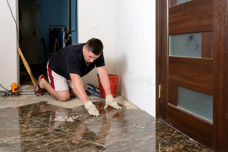 Man placing ceramic floor tile in position over adhesive royalty free stock image