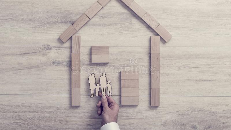 Man placing a cut out of his family inside a wood frame home in stock photos