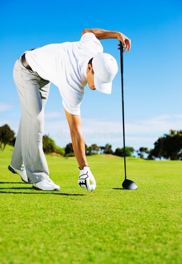 Man Placing Golf Ball on Tee royalty free stock photos