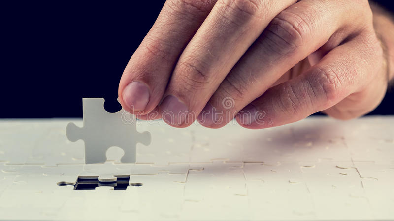 Man placing the last piece in the jigsaw puzzle. Close up of the hand of a man placing the last piece in place in a jigsaw puzzle conceptual of problem solving royalty free stock photo