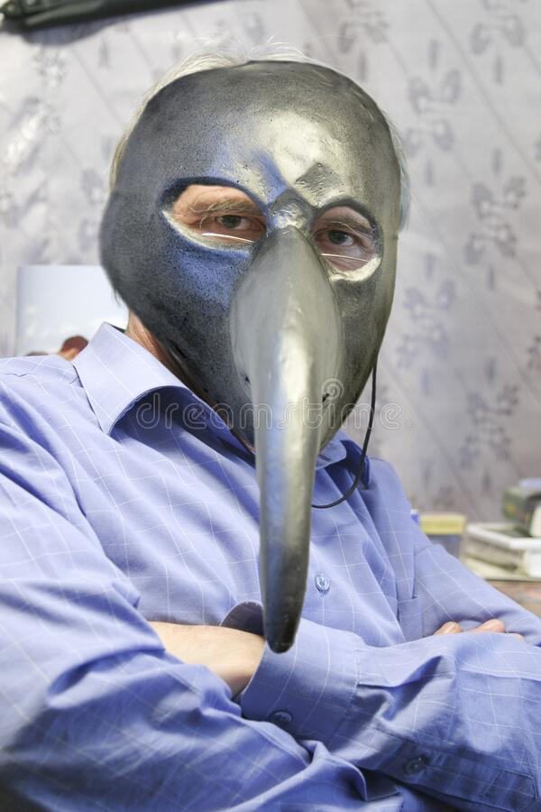 Man in a plague mask. Portrait of a man in a plague mask in a working environment royalty free stock photography