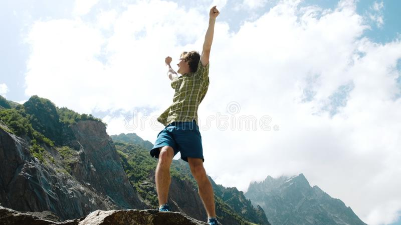 Happy man climbs a boulder and raises his hands up. Bouldering in the mountains stock image
