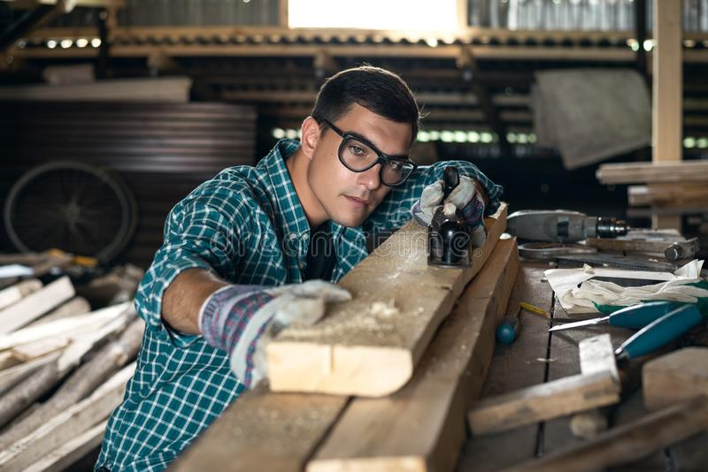 Man in a plaid shirt, goggles and gloves checks the quality of the planed board in the workshop, manual labor, home craftsman royalty free stock image