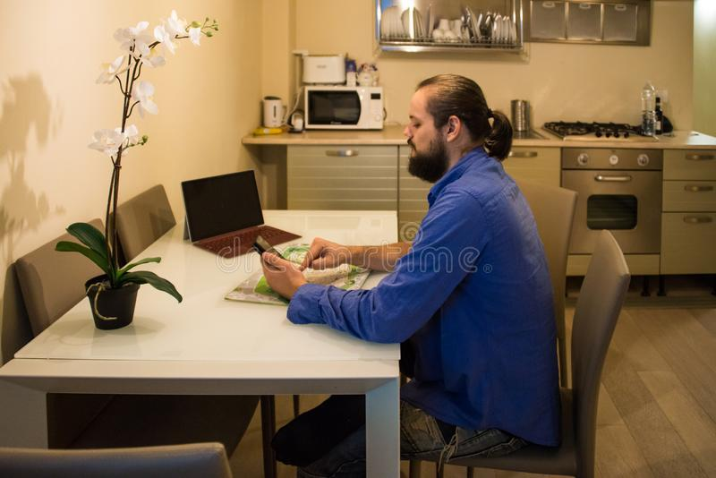 Man planning his vacation in his kitchen stock image