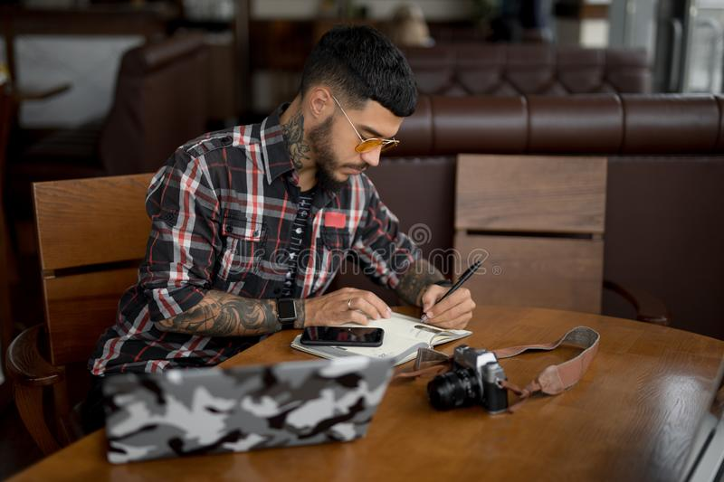 Man planning his working week making notes in a notebook royalty free stock image