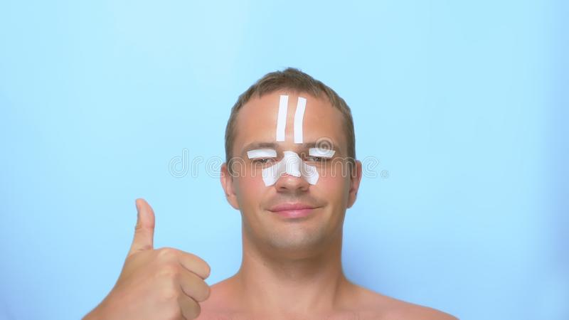 A man after a plastic surgery facelift, rhinoplasty, blepharoplasty. with a bandage on the nose, head and eyes. on blue stock image
