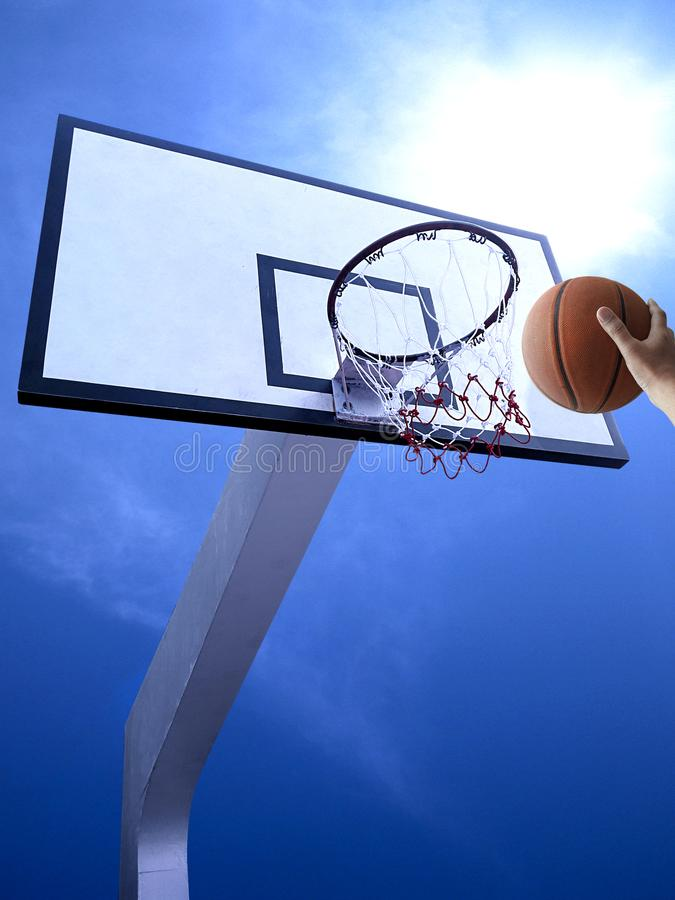 A man play basketball. Low angle view of basketball hoop against blue sky. For design In the media stock image
