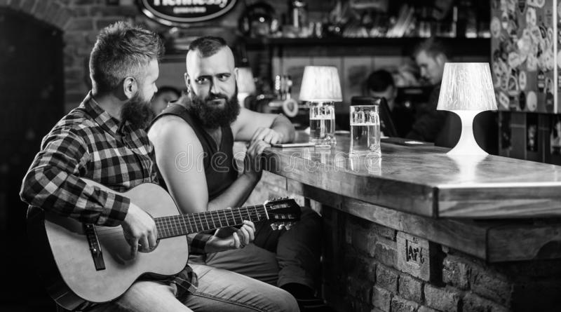 Man play guitar in bar. Cheerful friends relax with guitar music. Friday relaxation in bar. Friends relaxing in bar or. Pub. Real men leisure. Hipster brutal stock images